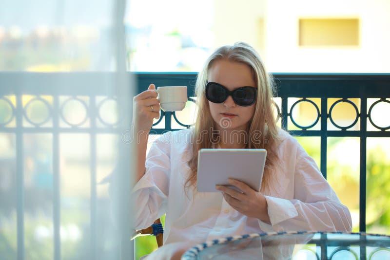 Женщина сидя читающ таблетк-ПК на балконе стоковое изображение