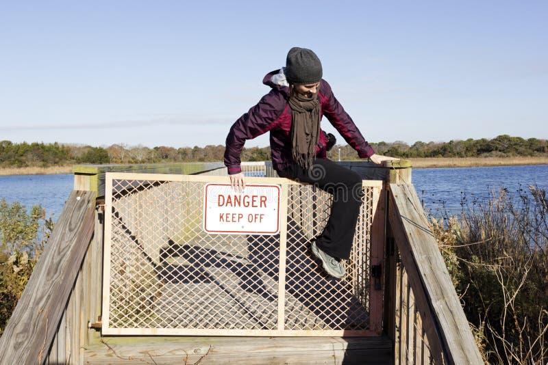 Женщина скача над загородкой стоковое фото