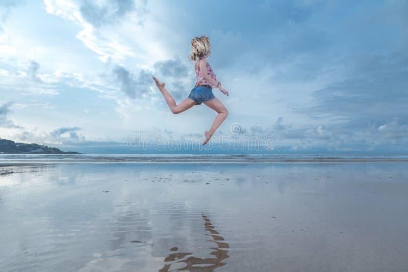 Женщина скача над водой стоковые фото