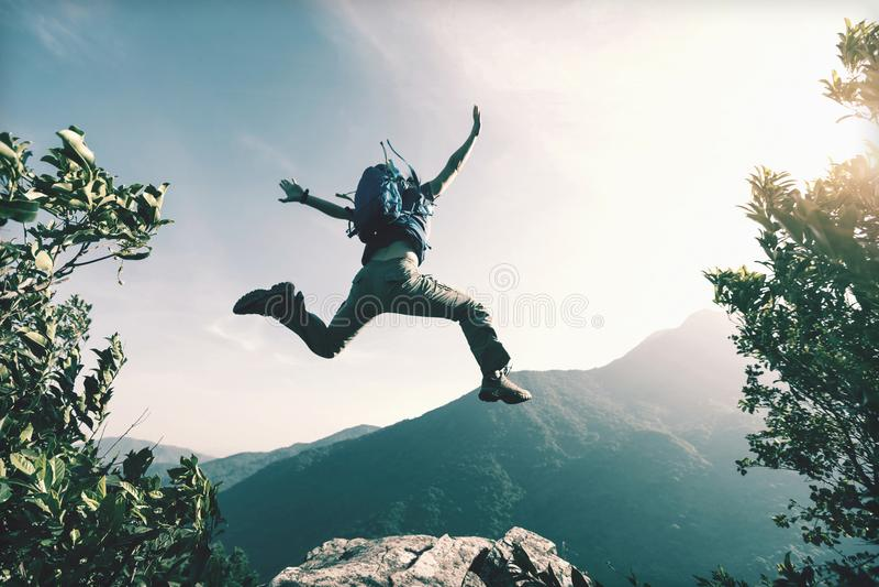 Женщина скача на край ` s скалы стоковое фото rf
