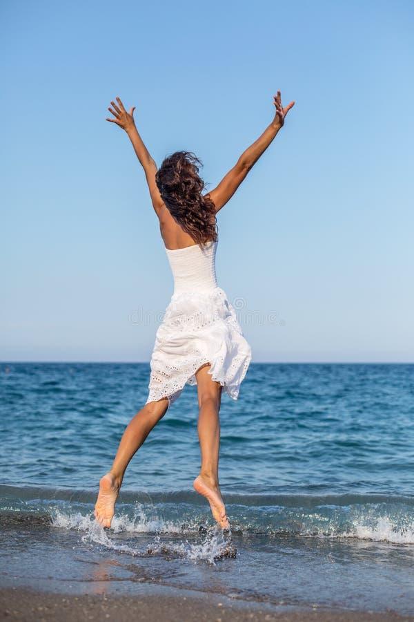 Женщина скача на пляж стоковое фото