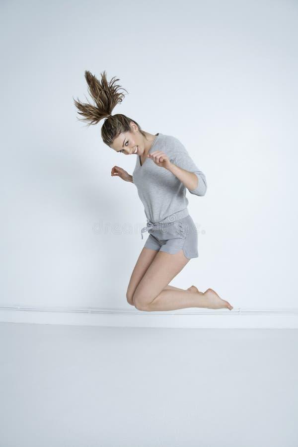 Женщина скача против покрашенной предпосылки стоковое изображение rf
