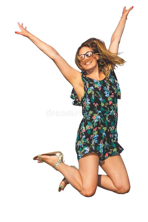 Женщина скача с утехой, изолированной на белой предпосылке С солнечными очками и усмехаться стоковое фото rf
