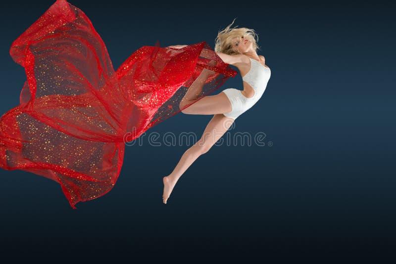 Женщина скача с silk тканью стоковая фотография rf