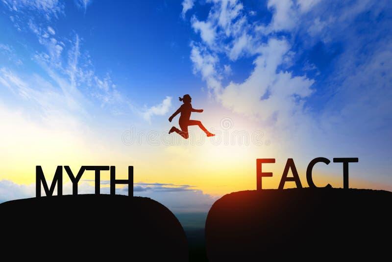 Женщина скачет через зазор между мифом к факту на заходе солнца стоковые фотографии rf