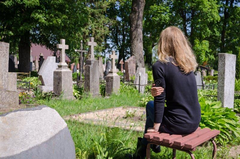 Женщина скорбы около усыпальницы супруга отца в кладбище стоковая фотография rf