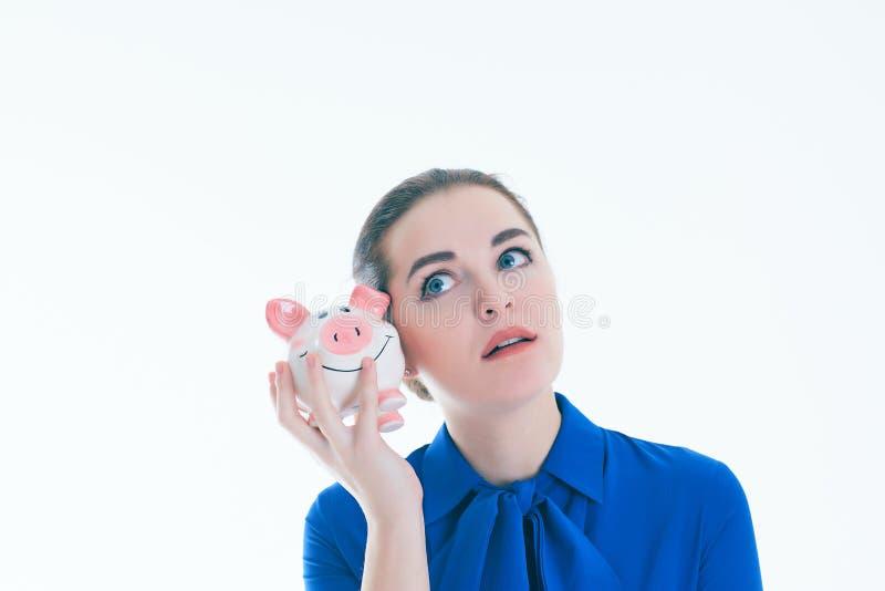 Женщина слушает к какому ` s внутри копилки Изолировано над белой предпосылкой стоковое изображение rf