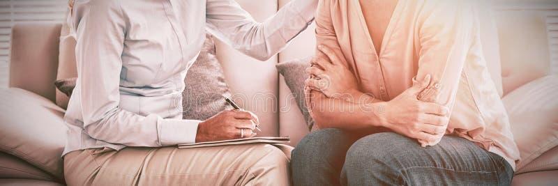 Женщина слушая к терапевту стоковое изображение