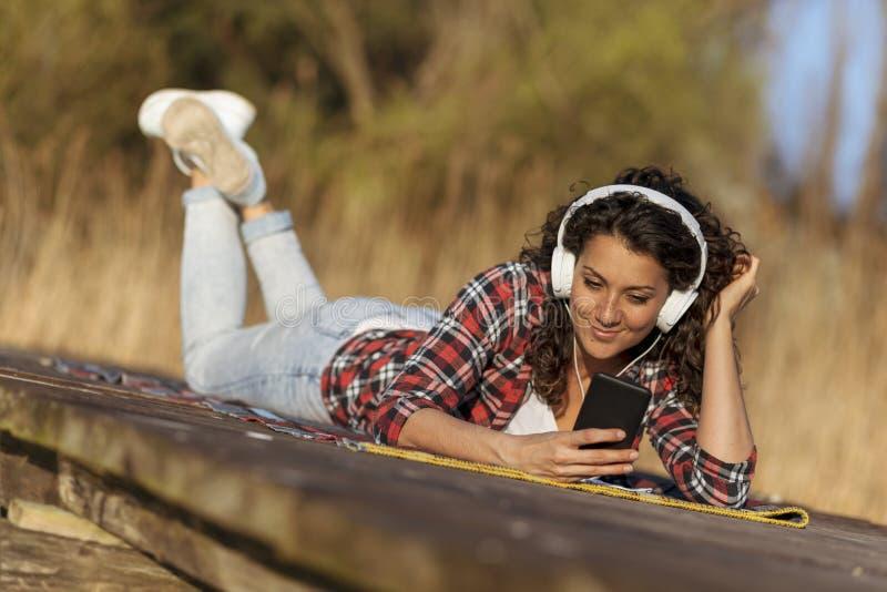 Женщина слушая музыку на доках озера стоковое фото