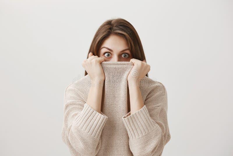 Женщина слышит, что ужасая рассказ делает ее дрожит из страха Портрет милой взрослой кавказской девушки пряча в свитере стоковые изображения rf
