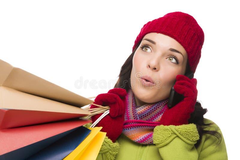 Женщина смешанной гонки держа хозяйственные сумки на смотреть сотового телефона стоковые фотографии rf