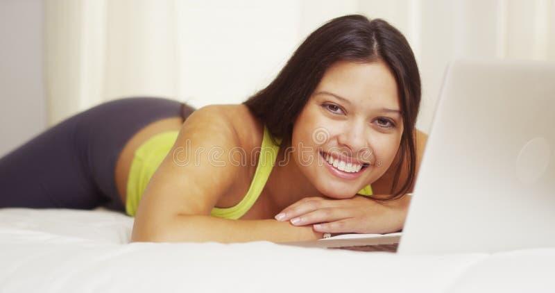 Женщина смешанной гонки усмехаясь с компьтер-книжкой на кровати стоковое фото