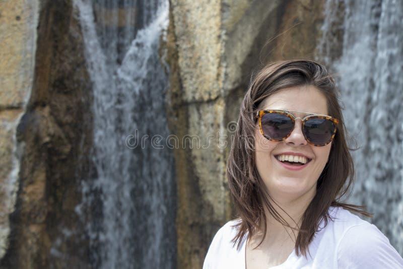 Женщина смеясь с предпосылкой водопада стоковые изображения