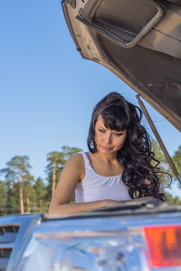Женщина смотрит заботливо на двигателе автомобиля стоковая фотография