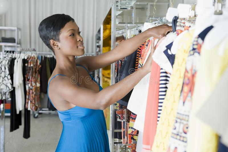 Женщина смотрит через рельс одежд стоковые фотографии rf