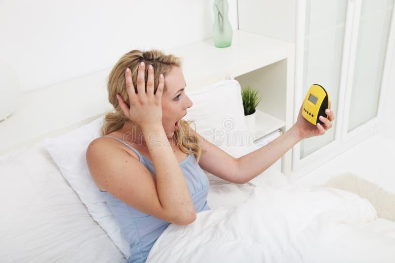 Женщина смотря будильник в ужасе стоковое изображение