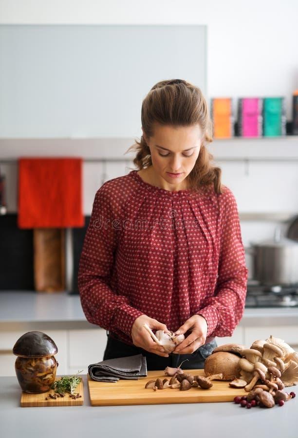 Женщина смотря вниз в кухне подготавливая чеснок и грибы стоковые фото
