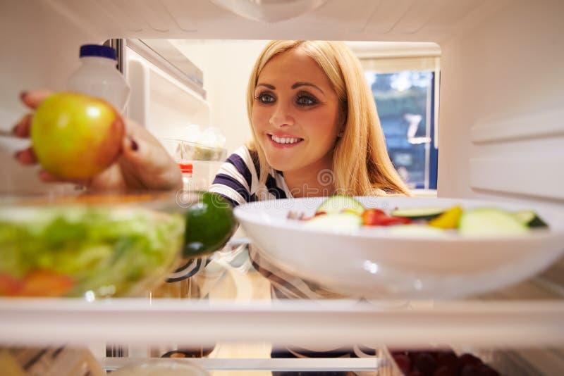 Женщина смотря внутренний холодильник вполне еды и выбирая Яблоко стоковое фото