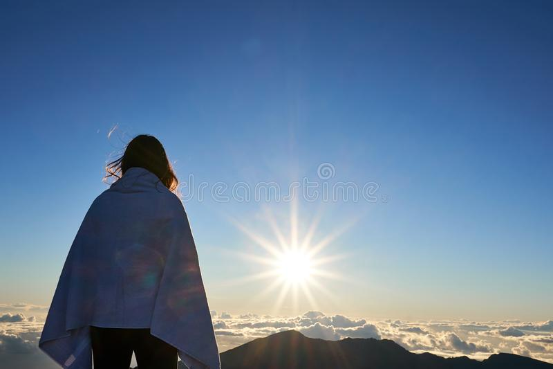 Женщина смотря горизонт на пиках горы Haleakala во время подъема солнца стоковое изображение rf