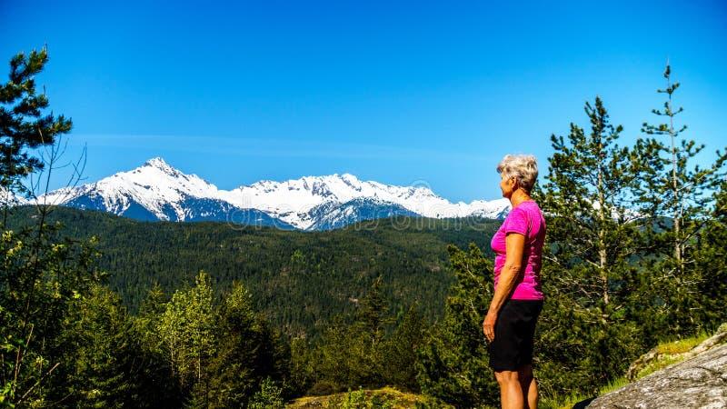 Женщина смотря горную цепь Tantalus с снегом покрыла пики горы альфы, Serratus и горы Tantalus стоковое изображение rf