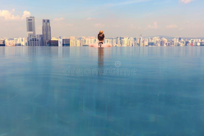 Женщина смотря городской пейзаж пока ослабляющ в пейзажном бассейне стоковое изображение