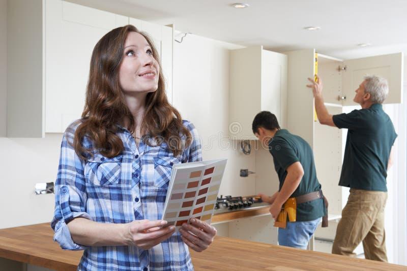 Женщина смотря диаграмму краски в новой кухне стоковые фотографии rf