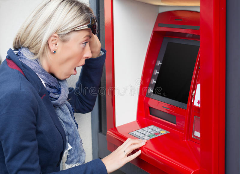 Женщина смотря ее баланс счета в банк стоковая фотография