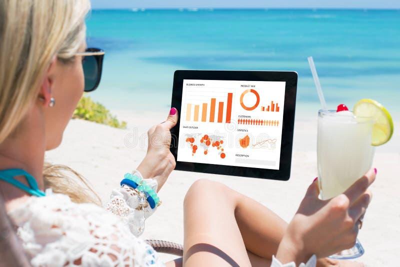 Женщина смотря диаграммы и диаграммы на цифровой таблетке стоковые фотографии rf