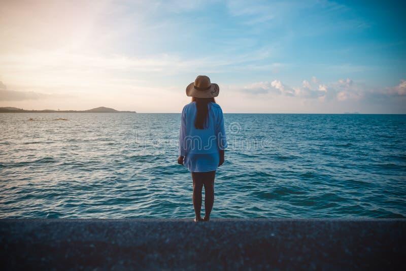 Женщина смотря и стоя на взгляде на пляже с морем и заходом солнца стоковое изображение