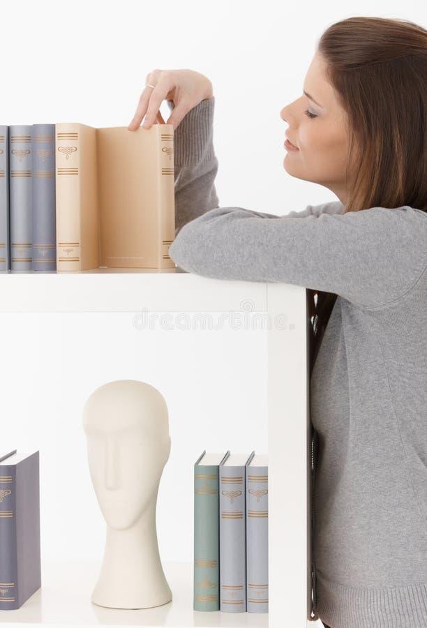 Женщина смотря книги на полке стоковые изображения rf