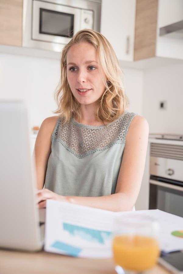 Женщина смотря компьтер-книжку ПК в кухне стоковые фотографии rf