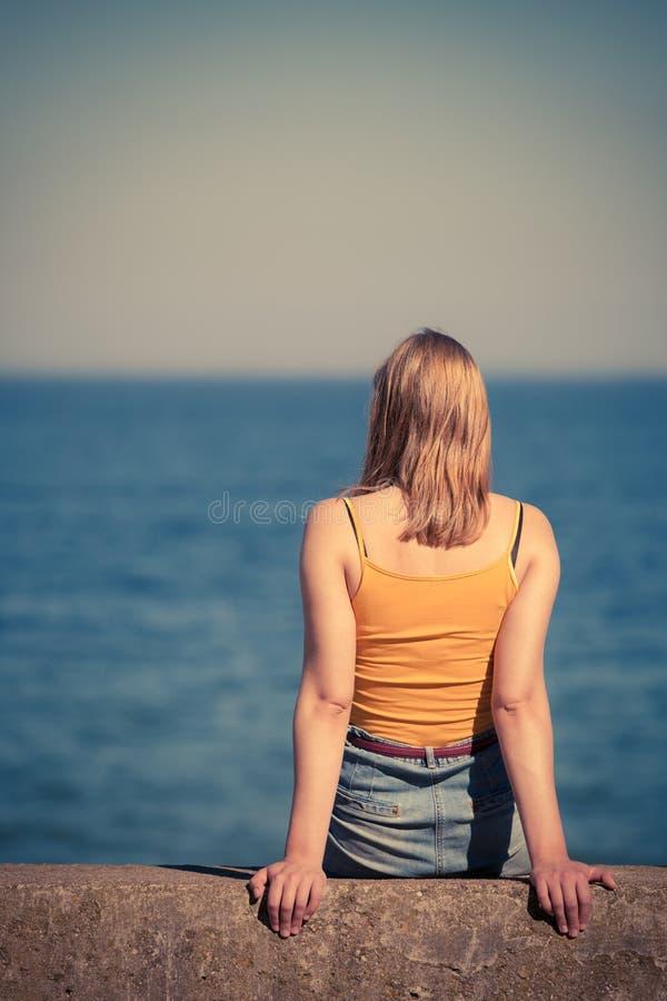 Женщина смотря к горизонту моря стоковые изображения