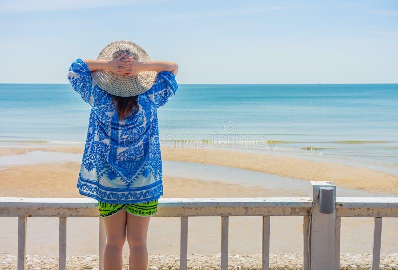 Женщина смотря на море и держа соломенную шляпу на голове на террасе набережной стоковые изображения rf
