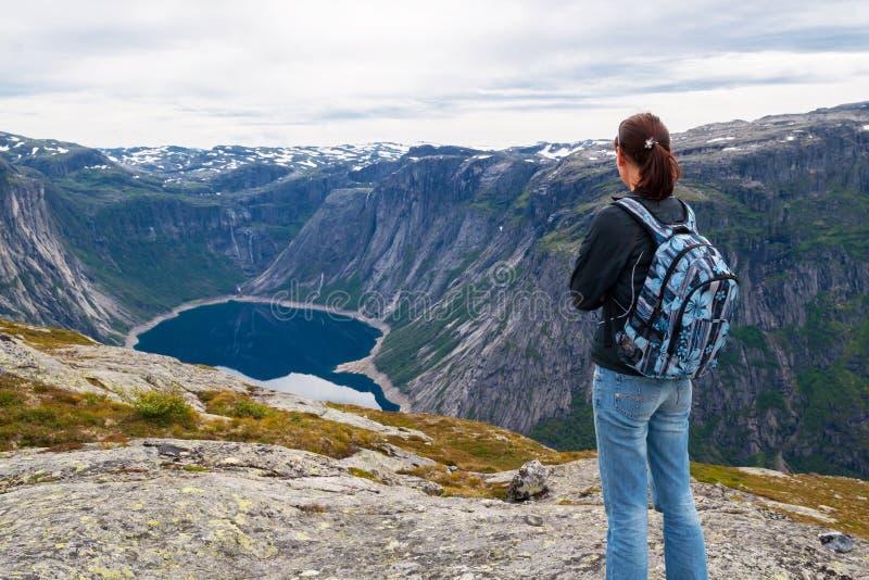 Женщина смотря озеро в горах, Норвегию Путь к Trol стоковое изображение rf