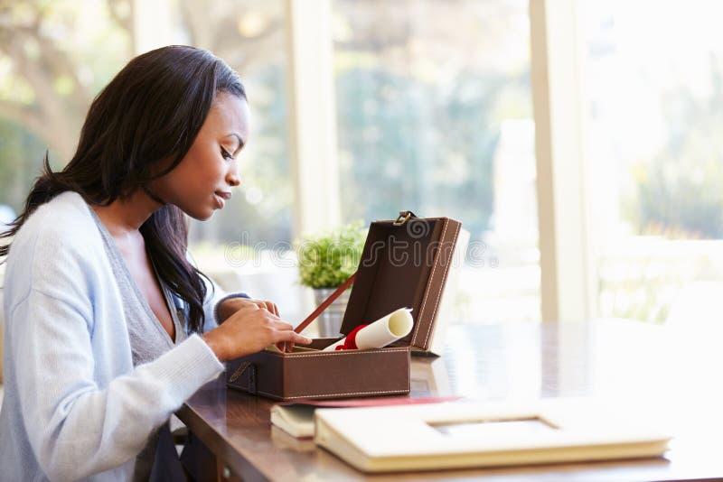 Женщина смотря документ в коробке Keepsake на столе стоковые изображения