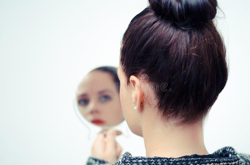 Женщина смотря отражение собственной личности в зеркале стоковая фотография rf