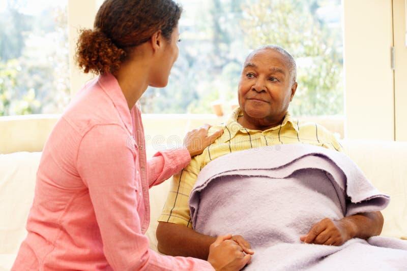 Женщина смотря после больного отца стоковое фото