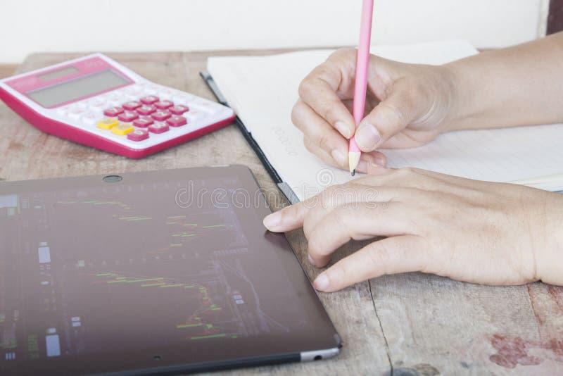 Женщина смотря таблетку для запаса торговца номера и показатель на тетради стоковые изображения rf