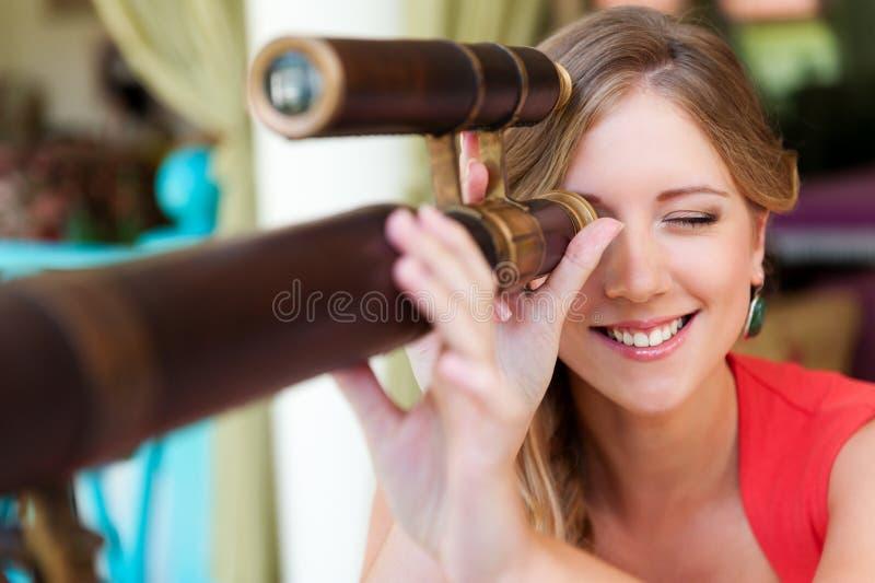 Женщина смотря через телескоп стоковые фотографии rf