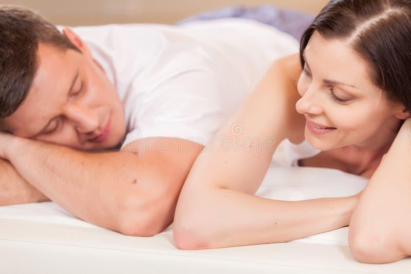 Женщина смотря человека и лежа в кровати стоковые изображения