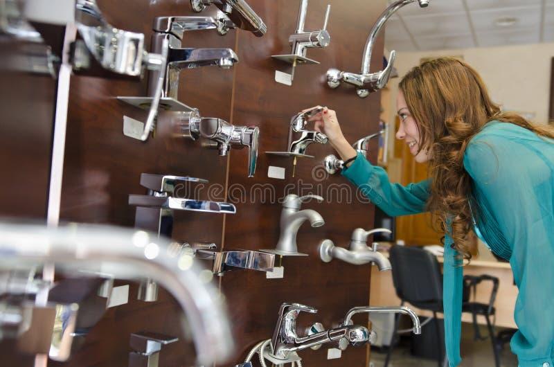 Женщина смотря faucets на магазине стоковая фотография