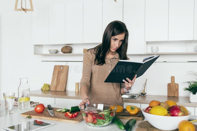 Женщина смотря foo поваренной книги салата овоща рецепта простое здоровое стоковые фотографии rf