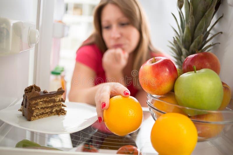 Женщина смущаясь ли съесть торт или апельсин стоковые изображения