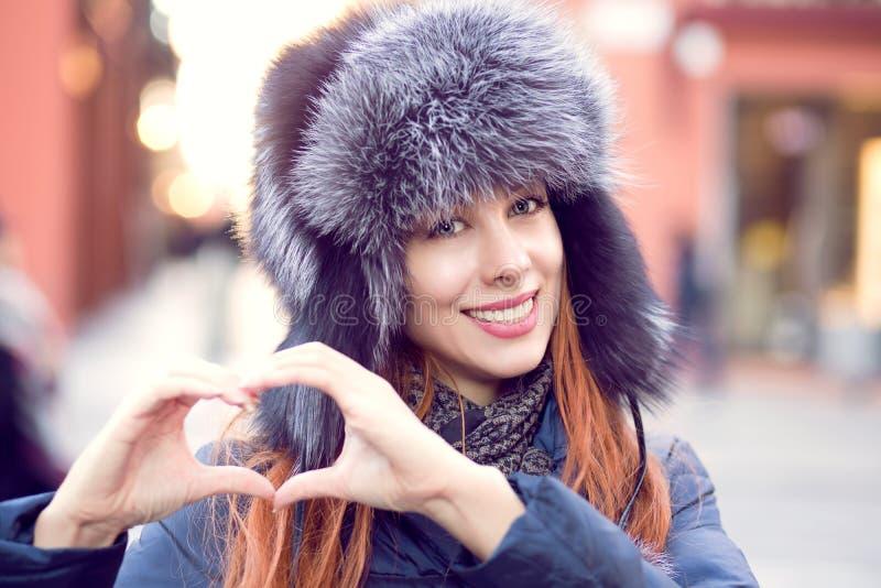 Женщина снаружи в меховой шапке зимы показывая форму сердца с рукой стоковая фотография