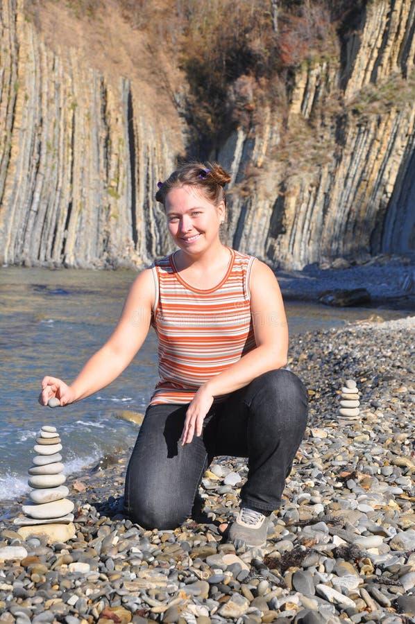 Женщина собирает пирамиду камней Краснодарская область, Россия стоковое изображение
