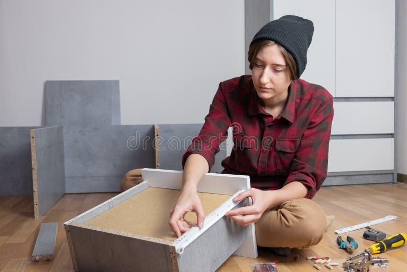 Женщина собирая ящик комода для новой мебели спальни стоковое изображение rf