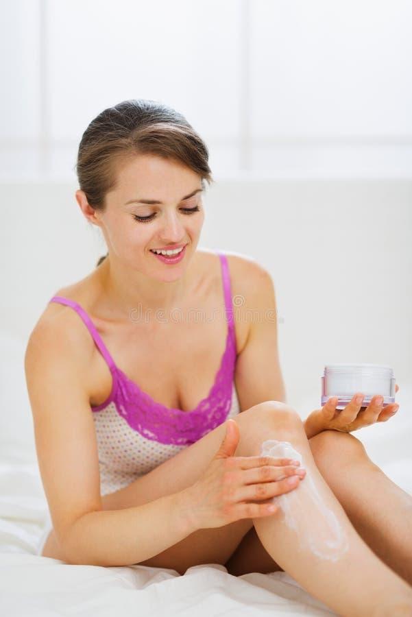 Женщина собственной личности заботя прикладывая creme на ноге стоковое изображение rf