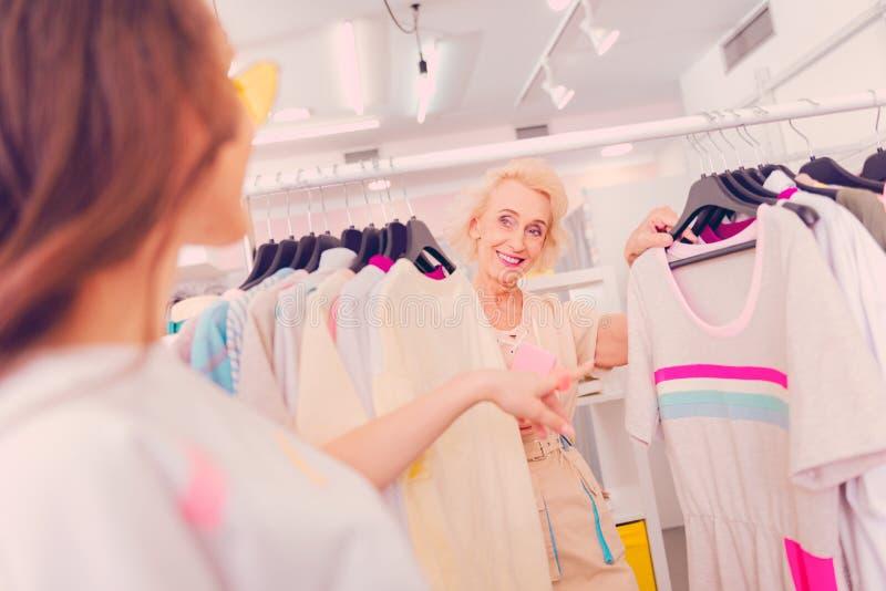 Женщина советуя с с ее другом о покупке платья стоковое фото rf