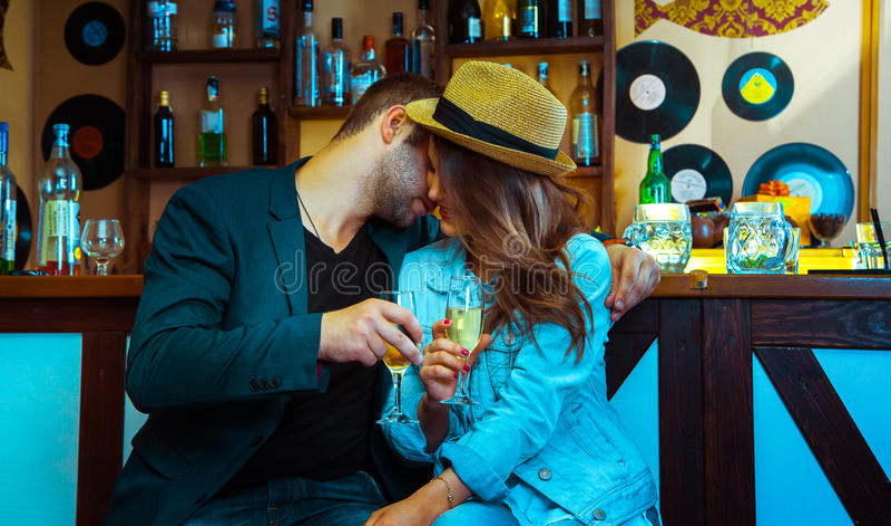 Женщина сокращая человека в баре и выпивая шампанское стоковые изображения rf