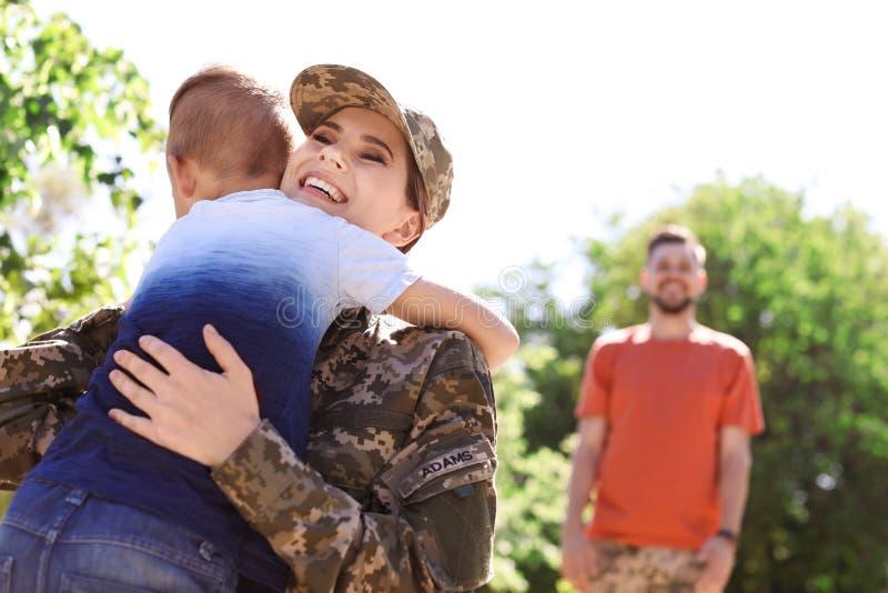 Женщина-солдат обнимая с ее сыном outdoors Военная служба стоковые изображения